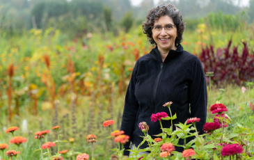 An image of Claire Kremen in a field of flowers. Photo by Richard Amies.