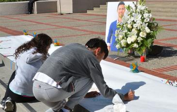Students sign a commemorative poster for Nicolas Leslie