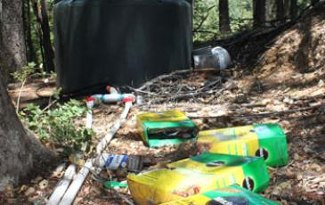Discarded fertilizer boxes with water tank in the background