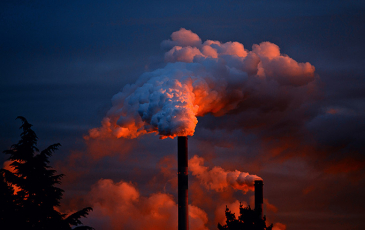 Smokestack emitting gases against a night skyline
