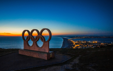 """Olympic """"rings"""" symbol sign in front of city landscape at night"""