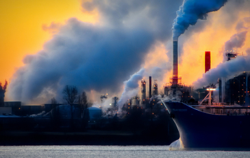 An industrial port with a cargo ship and smokestacks