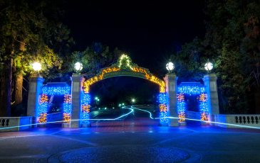 Sather gate lit up in blue and gold