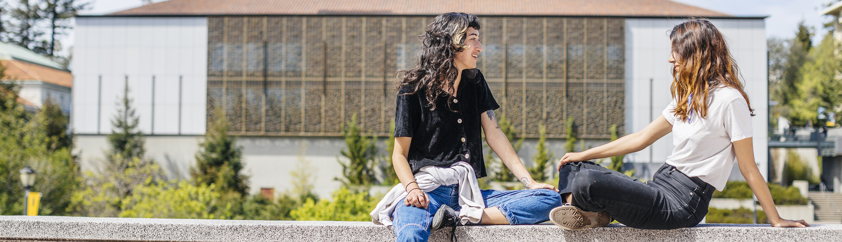 Two students sitting on the balustrade outside Moffitt Library overlooking Memorial Glade on the UC Berkeley campus.