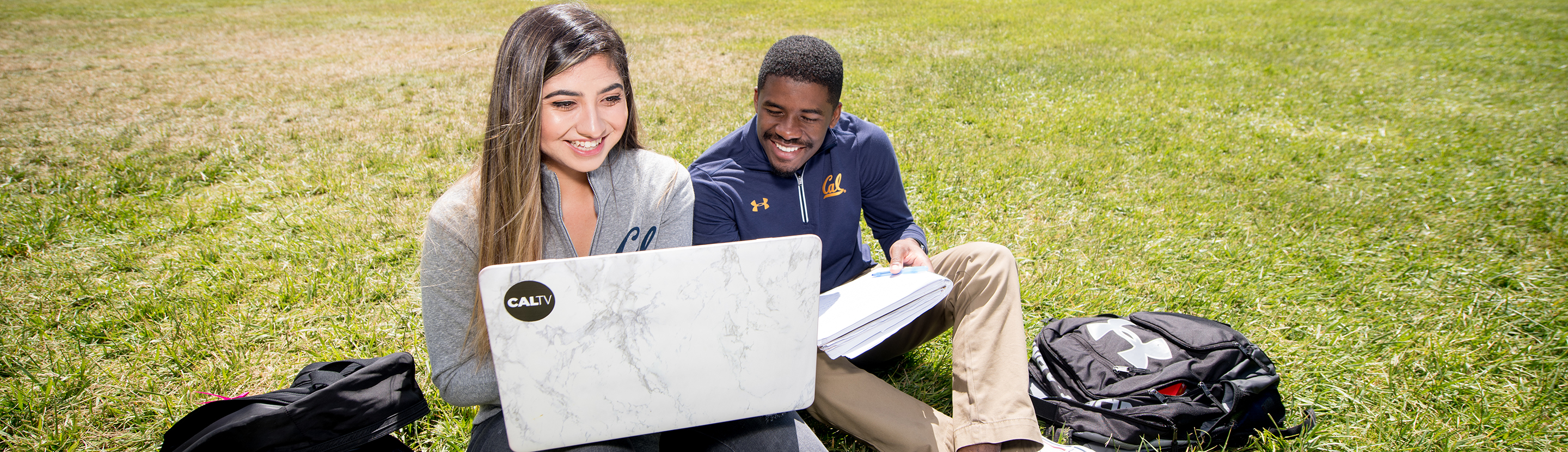 Students studying outdoors with laptop.
